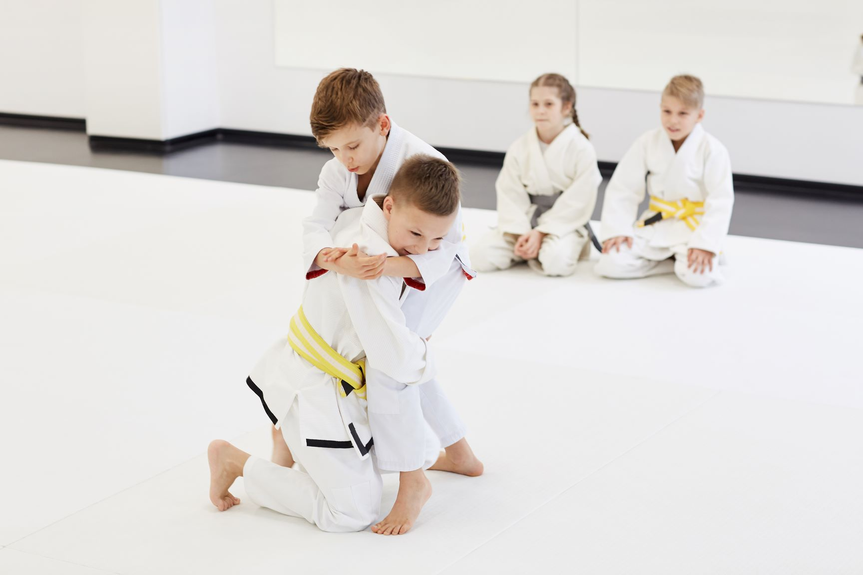 Two boys fighting while other children sitting on the floor and looking at them during competition in karate